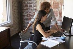 研究计算机的两名女实业家在办公室 免版税图库摄影