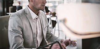 研究计算机的严肃的商人 免版税库存图片