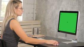 研究计算机的可爱的成熟女实业家在她的工作站 绿色屏幕大模型显示 股票录像
