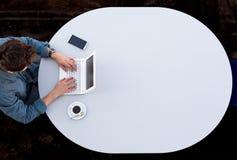 研究计算机的商人在办公室灰色圆桌顶视图 免版税库存照片