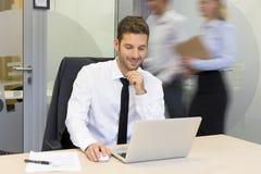 研究计算机的商人在办公室,商人movin 免版税库存照片