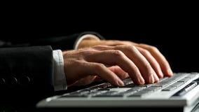 研究计算机的商人在打字在键盘旁边 图库摄影