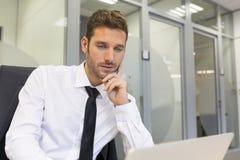 研究计算机的商人在现代办公室 免版税库存图片