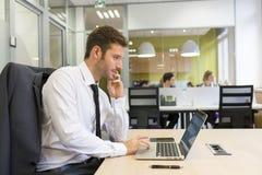 研究计算机的商人在现代办公室 免版税图库摄影