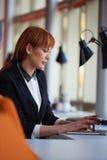 研究计算机的女商人在办公室 库存照片