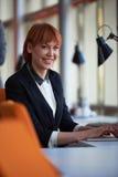 研究计算机的女商人在办公室 免版税库存图片