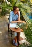 研究计算机的女商人在咖啡馆户外 做自由职业者工作 库存照片