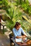 研究计算机的女商人在咖啡馆户外 做自由职业者工作 库存图片