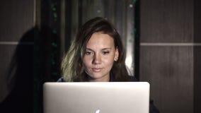 研究计算机的女孩在内部的晚上有水背景 股票视频
