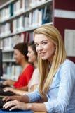 研究计算机的女孩在图书馆里 免版税库存照片
