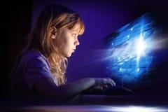 研究计算机的小白肤金发的女孩 免版税库存照片