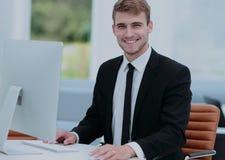 研究计算机的微笑的商人在一个现代办公室 免版税库存照片