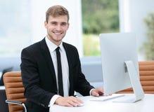研究计算机的微笑的商人在一个现代办公室 免版税库存图片