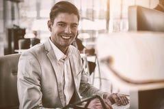 研究计算机的微笑的商人 库存照片