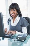 研究计算机的微笑的时髦的女实业家 库存照片