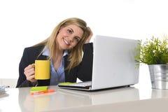 研究计算机的愉快的白肤金发的女商人在办公桌微笑 免版税图库摄影