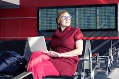 研究计算机的成人夫人在机场终端 免版税库存图片