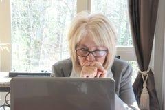 研究计算机的成熟的商业妇女。 免版税图库摄影