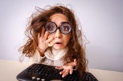 研究计算机的滑稽的书呆子女孩 免版税库存照片