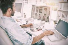 研究计算机的男性照片编辑程序在一个明亮的办公室 库存图片