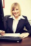研究计算机的白肤金发的女实业家在办公室 库存照片