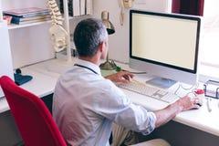 研究计算机的确信的男性医生在养老院诊所  库存照片