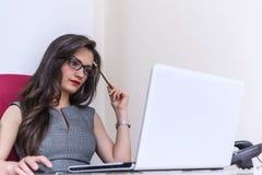 研究计算机的美丽的女商人在她的办公室 免版税库存图片