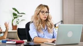 研究计算机的自由职业者妇女,当她的丈夫在背景中时观看一个局面 影视素材