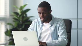 研究计算机的被聚焦的非裔美国人的商人在办公桌 股票视频