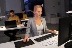 研究计算机的设计师在夜办公室 免版税图库摄影