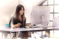 研究计算机的年轻亚裔图表设计师 免版税库存照片