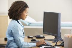 研究计算机的年轻女性医生在书桌 免版税库存照片