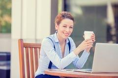 研究计算机膝上型计算机的妇女饮用的咖啡在公司办公室外 免版税库存照片