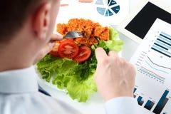 研究销售方针的商人特写镜头在工作午餐期间 免版税库存图片