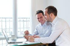 研究项目的两个微笑的愉快的商人 免版税库存照片