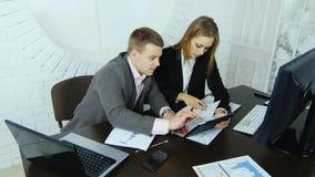 研究项目的年轻女商人在一张书桌在会议室与她的助理一起 股票录像