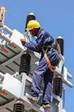 研究高压输电线的电工 免版税图库摄影