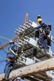 研究高压输电线的电工 免版税库存照片