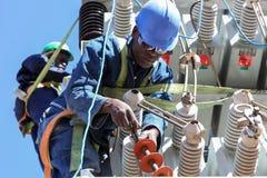 研究高压输电线的电工 免版税库存图片