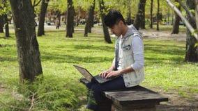 研究黑膝上型计算机的人自由职业者在公园 股票录像