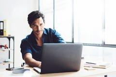 研究移动计算机的微笑的商人在晴朗的办公室 键入在笔记本键盘的工友 水平,弄脏 库存图片