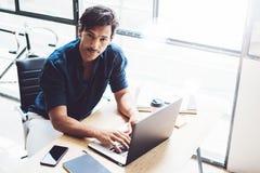 研究移动计算机的成人英俊的商人在晴朗的办公室 键入在笔记本键盘的工友 水平 免版税库存图片