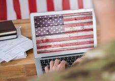 研究他的有美国国旗的膝上型计算机的商人 免版税库存图片