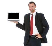 研究他的膝上型计算机的英俊的年轻商人 库存照片