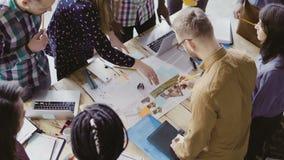 研究建筑项目的年轻队顶视图 小组站立近的桌和谈论的混合的族种人 股票录像