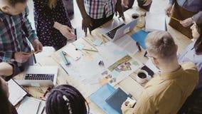 研究建筑项目的年轻队顶视图 小组站立近的桌和谈论的混合的族种人 免版税库存图片