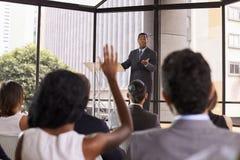 给研讨会的黑商人采取观众问题 免版税图库摄影