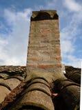 砖反对的烟囱和赤土陶器瓦云彩和天空背景  免版税图库摄影
