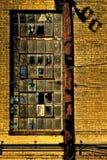 砖墙、电线杆和残破的窗口 库存照片