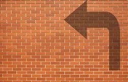 砖墙与箭头的难看的东西背景在砖墙上 免版税库存图片